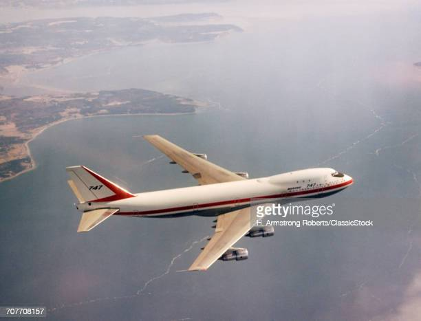 1970s BOEING 747 AIRPLANE OVER WATER TRANSPORTATION COMMERCIAL AVIATION AIR TRAVEL