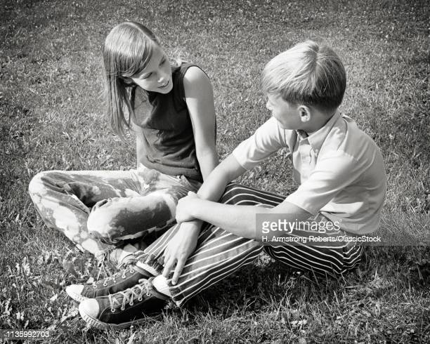 1970s BOY AND GIRL SITTING...