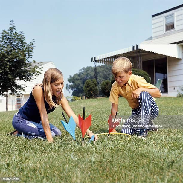 1970s BOY GIRL PLAYING LAWN DARTS GAME IN BACKYARD