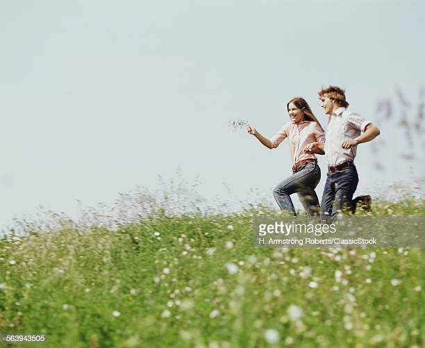 1970s BOY GIRL RUNNING FIELD