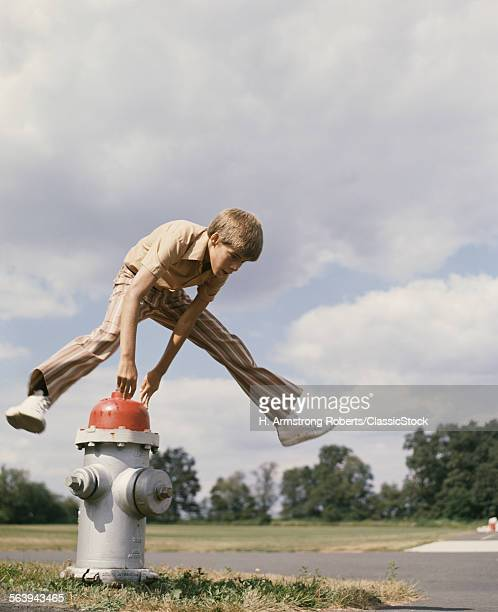 1970s BOY JUMPING FIRE HYDRANT