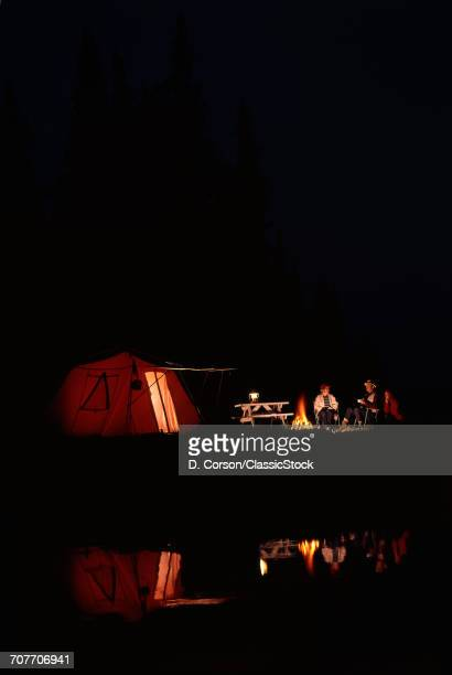 1970s CAMPERS SITTING OUTSIDE TENT AT NIGHT BY CAMPFIRE