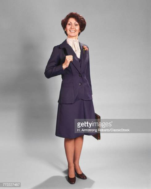 1970s CONFIDENT HAPPY SMILING BUSINESSWOMAN STANDING WEARING BLUE BUSINESS SUIT HOLDING BRIEFCASE LOOKING AT CAMERA