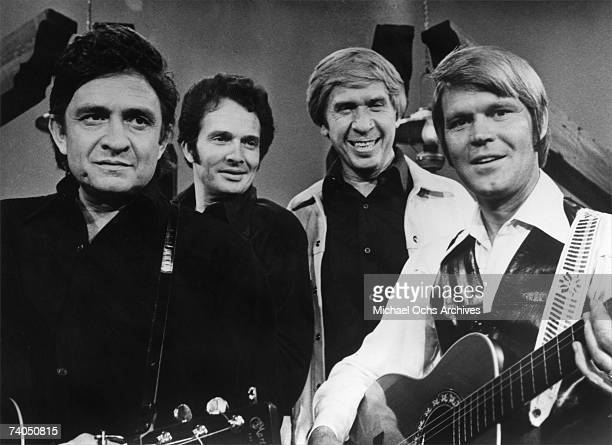 Country musician Johnny Cash, Merle Haggard, Buck Owens and Glen Campbell perform on stage during a mid 1970's performance for a TV show.