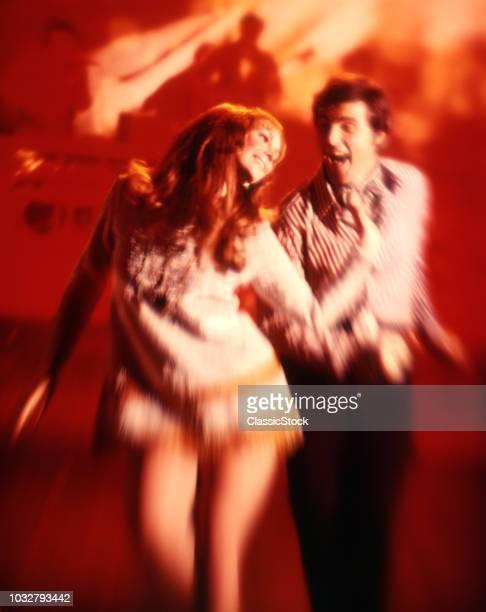 1970s COUPLE MAN WOMAN DISCO DANCING IN RED FLASHING LIGHTS