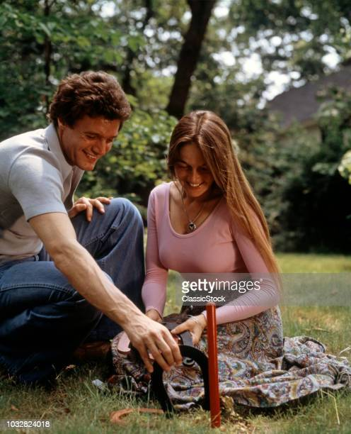 1970s COUPLE MAN WOMAN OUTDOORS YARD LAWN SUMMER PLAYING HORSESHOES