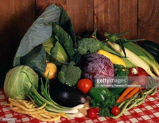 1970s DISPLAY OF FRESH GARDEN VEGETABLES ON RED CHECKERED TABLECLOTH