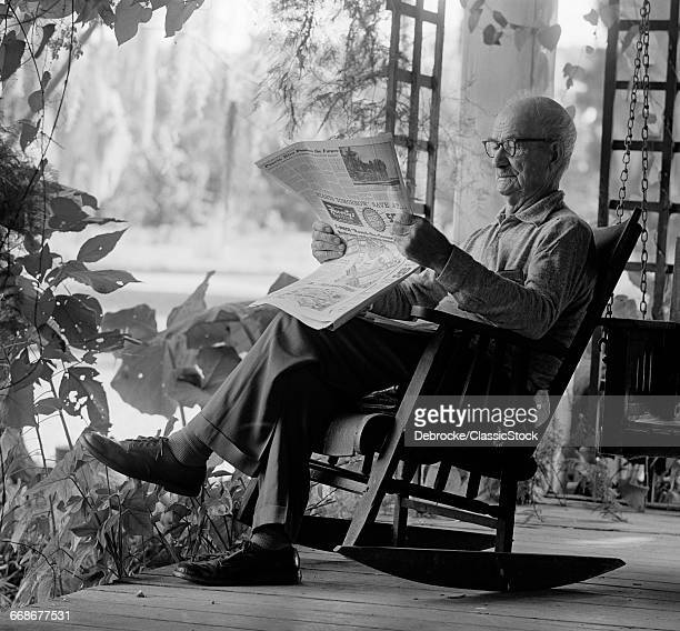 1970s ELDERLY MAN IN ROCKER READING NEWSPAPER ON PORCH