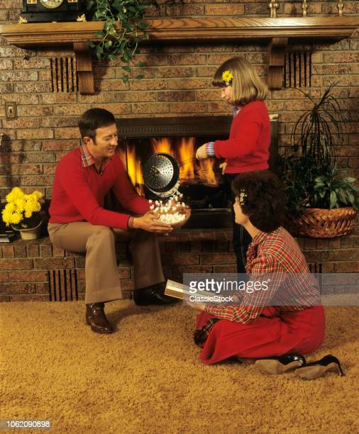 1970s FAMILY FATHER MAN MOTHER WOMAN DAUGHTER GIRL MAKING POPCORN FIREPLACE ORANGE SHAG RUG HAPPY SMILING