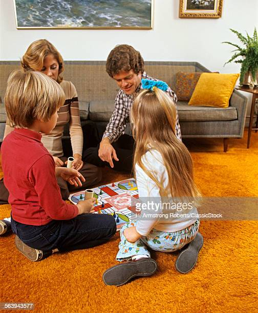 1970s FAMILY MOTHER FATHER SON DAUGHTER PLAYING BOARD GAME IN LIVING ROOM SITTING ON FLOOR SHAG CARPET