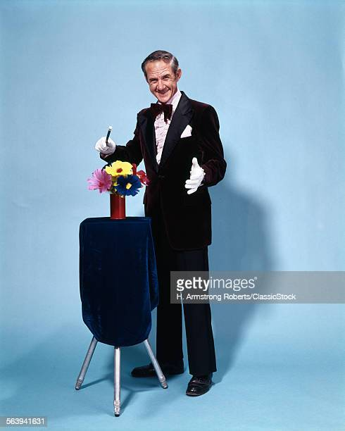 1970s FULL LENGTH SMILING MAGICIAN WAVING WAND OVER FLOWERS LOOKING AT CAMERA