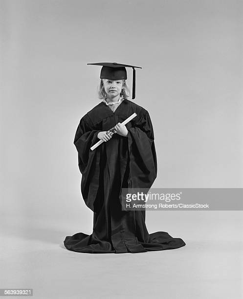 1970s GIRL WEARING GRADUATION CAP GOWN HOLDING DIPLOMA