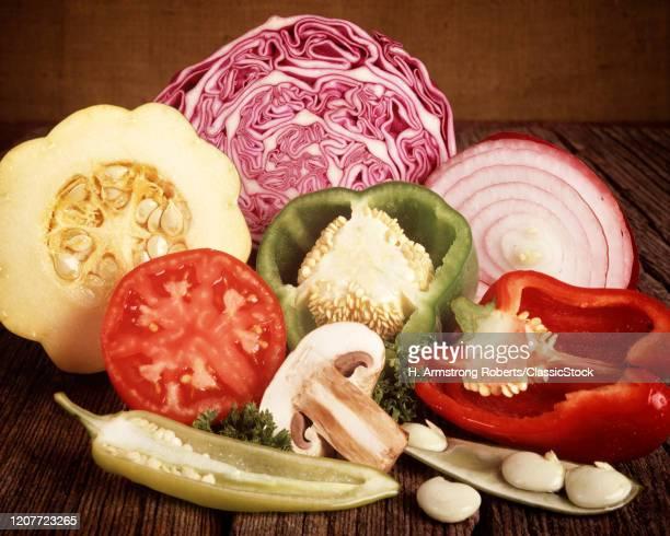 1970s half slices garden produce vegetables on brown burlap background: tomato, cabbage, onion, pepper, beans, mushroom, squash.