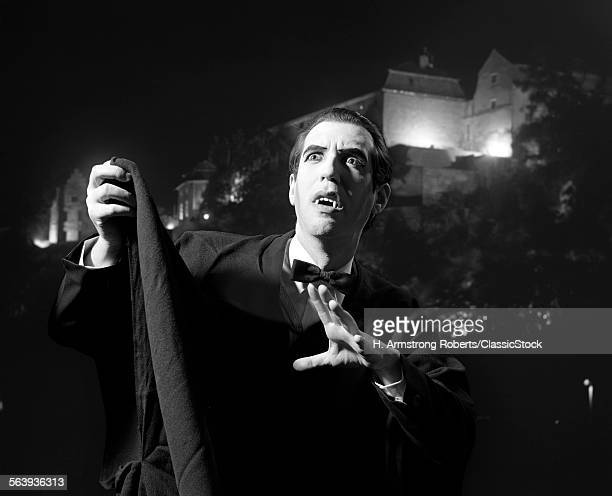 1970s HALLOWEEN NIGHTTIME PORTRAIT OF MAN WEARING CAPE AND FANGS DRESSED AS DRACULA THE VAMPIRE