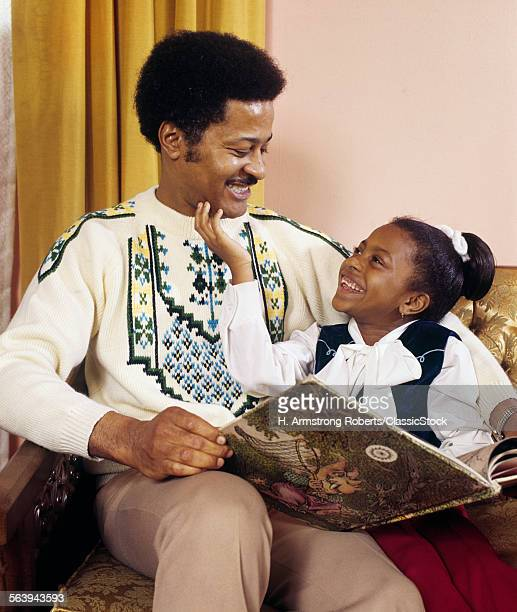 1970s HAPPY AFRICAN AMERICAN FATHER AND DAUGHTER READING A BOOK