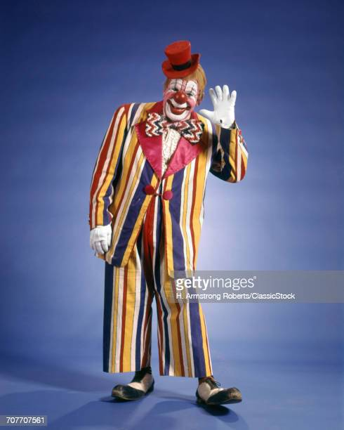 1970s HAPPY WAVING CIRCUS CLOWN STRIPED COLORFUL SUIT SMALL TOP HAT BIG BOW TIE FUNNY SHOES LOOKING AT CAMERA