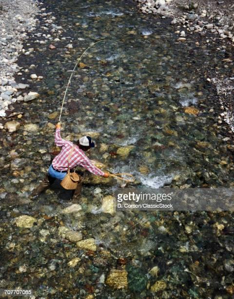 1970s MAN FISHERMAN SWIFT CURRENT LAKE GLACIER NATIONAL PARK MONTANA