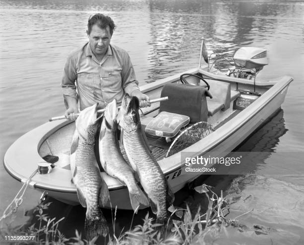1970s MAN IN SMALL MOTORBOAT AT EDGE OF LAKE LOOKING AT CAMERA HOLDING UP CATCH OF THREE LARGE MUSKIES