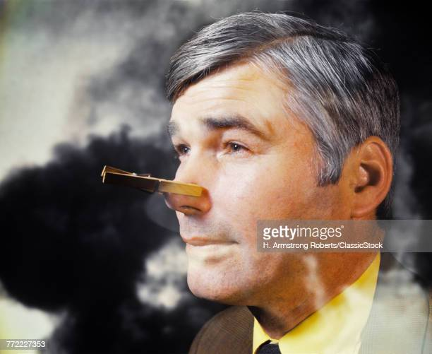 1970s MAN IN SMOKE BAD ATMOSPHERE WITH CLOTHESPIN ON HIS NOSE BECAUSE OF SMELL ODOR POLLUTION