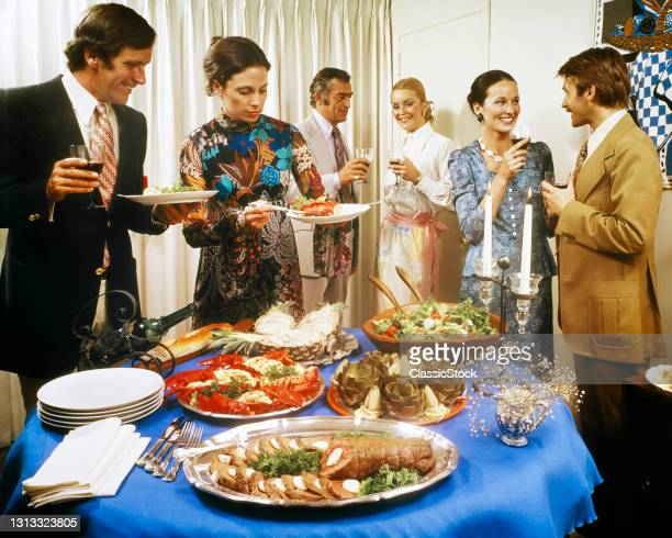1970s Men And Women Around A Party Buffet Table Talking Drinking Wine Table Set With Salad Artichokes Lobster Roast Beef Fondue.