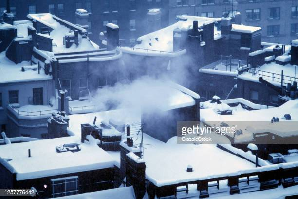 1970s Moody Soft Winter Early Morning Light Scene Overlooking Snow Covered City Rooftops Escaping Steam Heat New York City USA