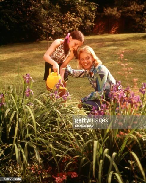 1970s MOTHER CHILD BACKYARD IRIS FLOWER GARDEN DAUGHTER HOLDING YELLOW WATERING CAN