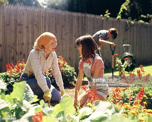 1970s MOTHER DAUGHTER AND SON GARDENING IN BACKYARD