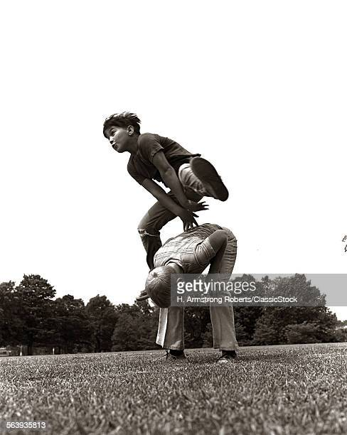 1970s PAIR OF BOYS OUTSIDE IN FIELD PLAYING LEAPFROG