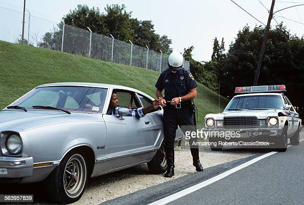 1970s POLICE OFFICER CHECKING DRIVERS LICENSE OF AFRICAN AMERICAN DRIVER ON SIDE OF ROAD