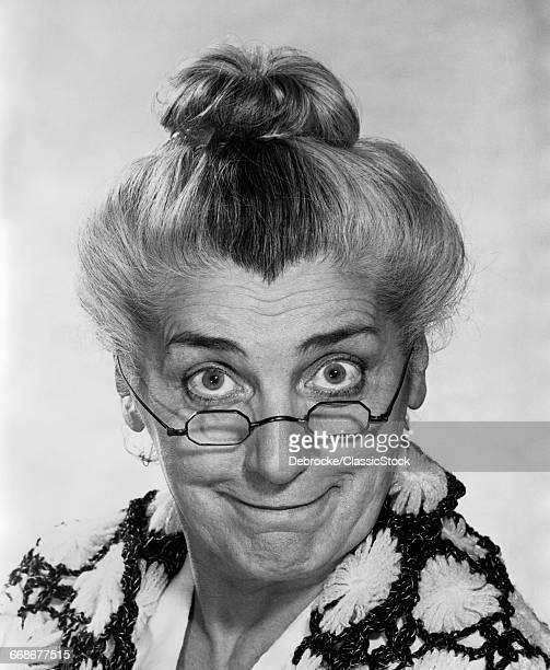 1970s PORTRAIT ELDERLY WOMAN WITH HAIR IN BUN WEARING GRANNY GLASSES SMILING LOOKING AT CAMERA