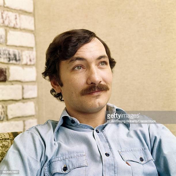 1970s PORTRAIT MAN WITH BROWN HAIR MOUSTACHE WEARING DENIM SHIRT