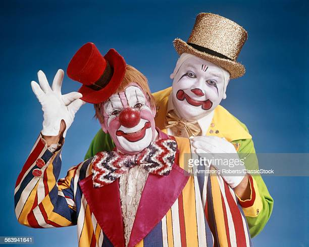1970s PORTRAIT OF TWO SMILING CLOWNS LOOKING AT CAMERA