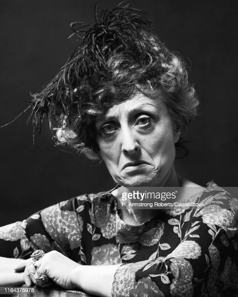 1970s Portrait Senior Woman With Mean Sour Sad Angry Facial Expression Wearing A Feathered Hat Looking At Camera
