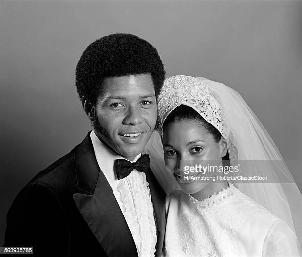 1970s PORTRAIT SMILING AFRICAN AMERICAN BRIDE GROOM WITH ARMS AROUND EACH OTHER LOOKING AT CAMERA