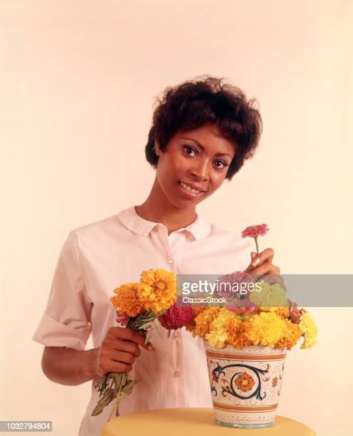 1970s PORTRAIT SMILING AFRICAN AMERICAN WOMAN ARRANGING FLOWERS