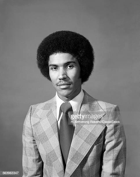 1970s SERIOUS AFRICAN AMERICAN MAN PORTRAIT WITH AFRO HAIR STYLE LOOKING AT CAMERA WEARING PLAID JACKET WITH VERY WIDE LAPELS