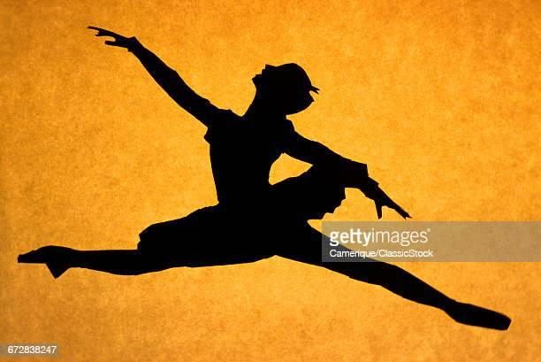1970s SILHOUETTED ANONYMOUS BALLERINA JUMPING A GRAND JETE AGAINST ORANGE BACKGROUND