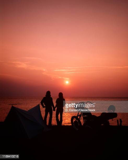 1970s SILHOUETTED ANONYMOUS COUPLE HOLDING HANDS LOOKING INTO SUNSET OVER WATER CAMPSITE TENT AND MOTORCYCLE