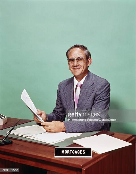 1970s SMILING MAN AT DESK...