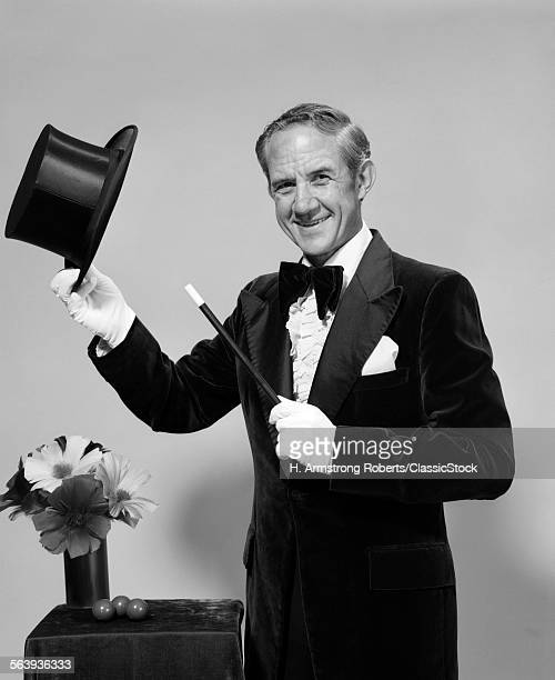 1970s SMILING MAN MAGICIAN WEARING VELVET TUXEDO WHITE GLOVES POINTING MAGIC WAND AT TOP HAT LOOKING AT CAMERA