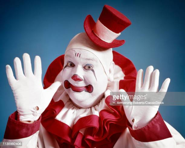 1970s SMILING PORTRAIT OF CLOWN LOOKING AT CAMERA WEARING TINY TOP HAT HOLDING UP HAPPY HANDS IN WHITE GLOVES
