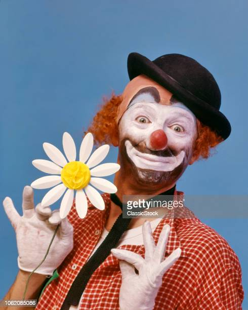 1970s SMILING WIDEEYED WHITE FACE HOBO CLOWN WITH RED NOSE LOOKING AT CAMERA WEARING A DERBY HAT AND HOLDING A PAPER DAISY