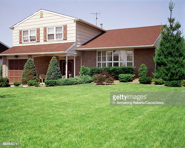 1970s SPLIT LEVEL SUBURBAN HOME WITH TELEVISION AERIAL BAY WINDOW MANICURED LAWN LANDSCAPING