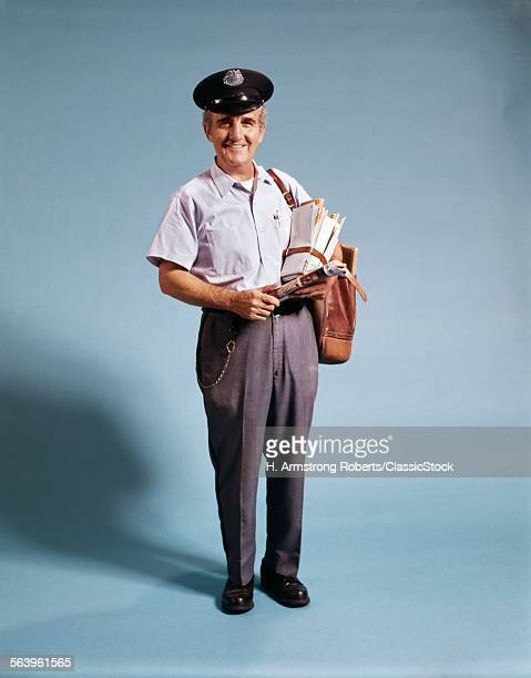 1970s STANDING FULL LENGTH PORTRAIT OF MIDDLE AGED MAILMAN CARRYING MAIL BAG WEARING UNIFORM LOOKING AT CAMERA