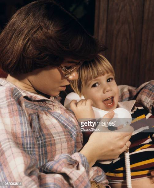 1970s TEENAGE GIRL BABY SITTER LETTING SMALL HAPPY BOY TALK ON TELEPHONE