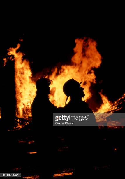 1970s Two Anonymous Firemen Silhouetted By Fire