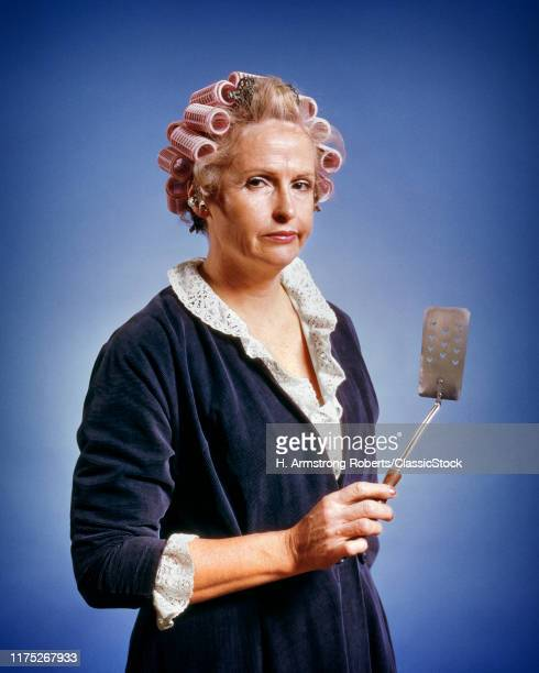 1970s WOMAN HOUSEWIFE LOOKING AT CAMERA WEARING HOUSECOAT CURLERS IN HAIR HOLDING AN EGG TURNER SPATULA GRUMPY FACIAL EXPRESSION