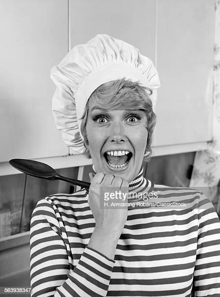 1970s WOMAN PORTRAIT WEARING CHEF'S TOQUE IN KITCHEN WITH SURPRISED FACE LOOKING AT CAMERA