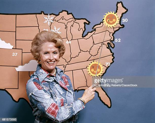 1970s WOMAN REPORTING WEATHER POINTING TO WEATHER MAP LOOKING AT CAMERA TELEVISION