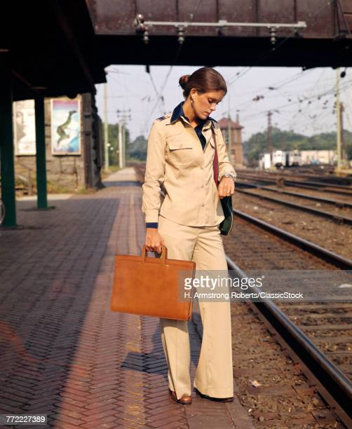 1970s YOUNG BUSINESSWOMAN ON TRAIN PLATFORM LOOKING AT WATCH BRIEFCASE COMMUTER